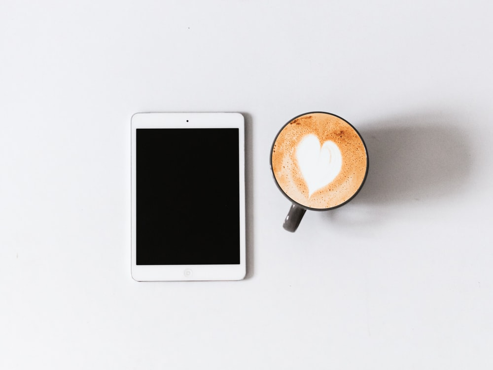 white iPad beside black ceramic mug