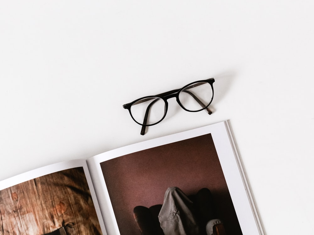 eyeglasses on top of photo album on white surface
