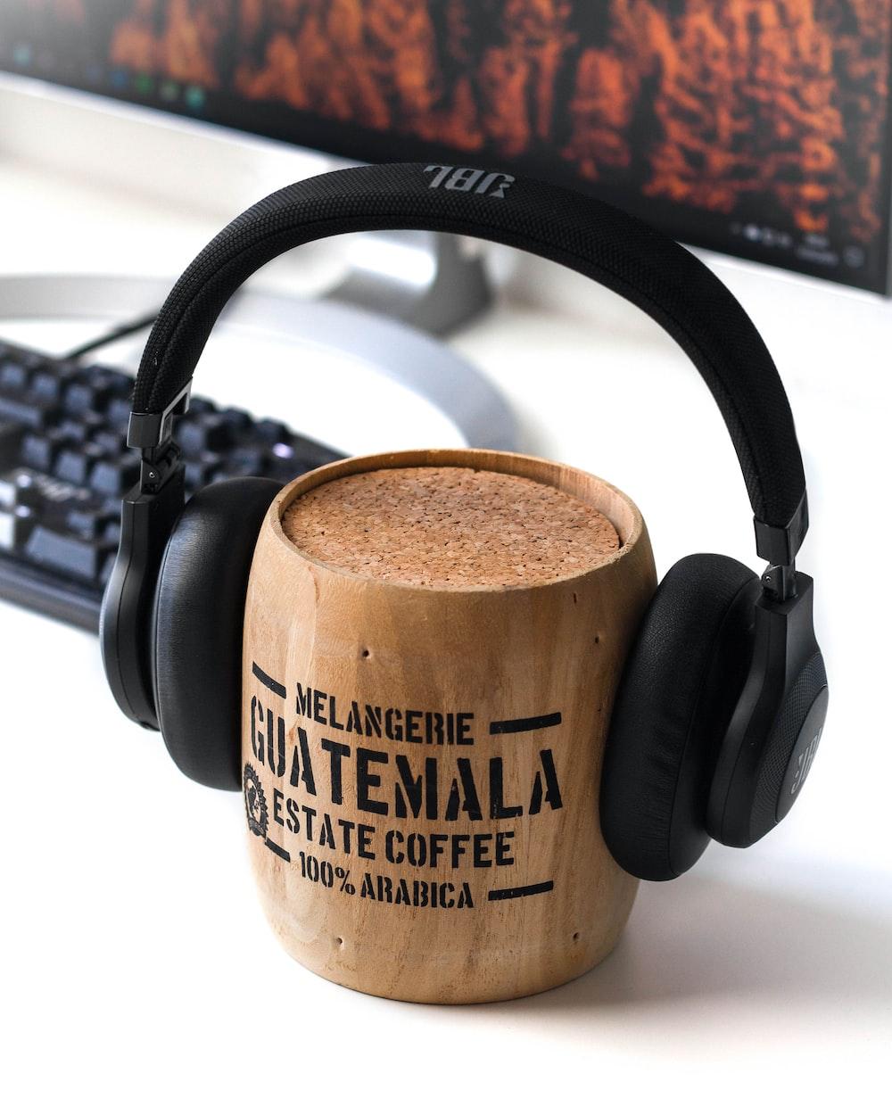 brown Guatemala wooden mug and black JBL headphones on it