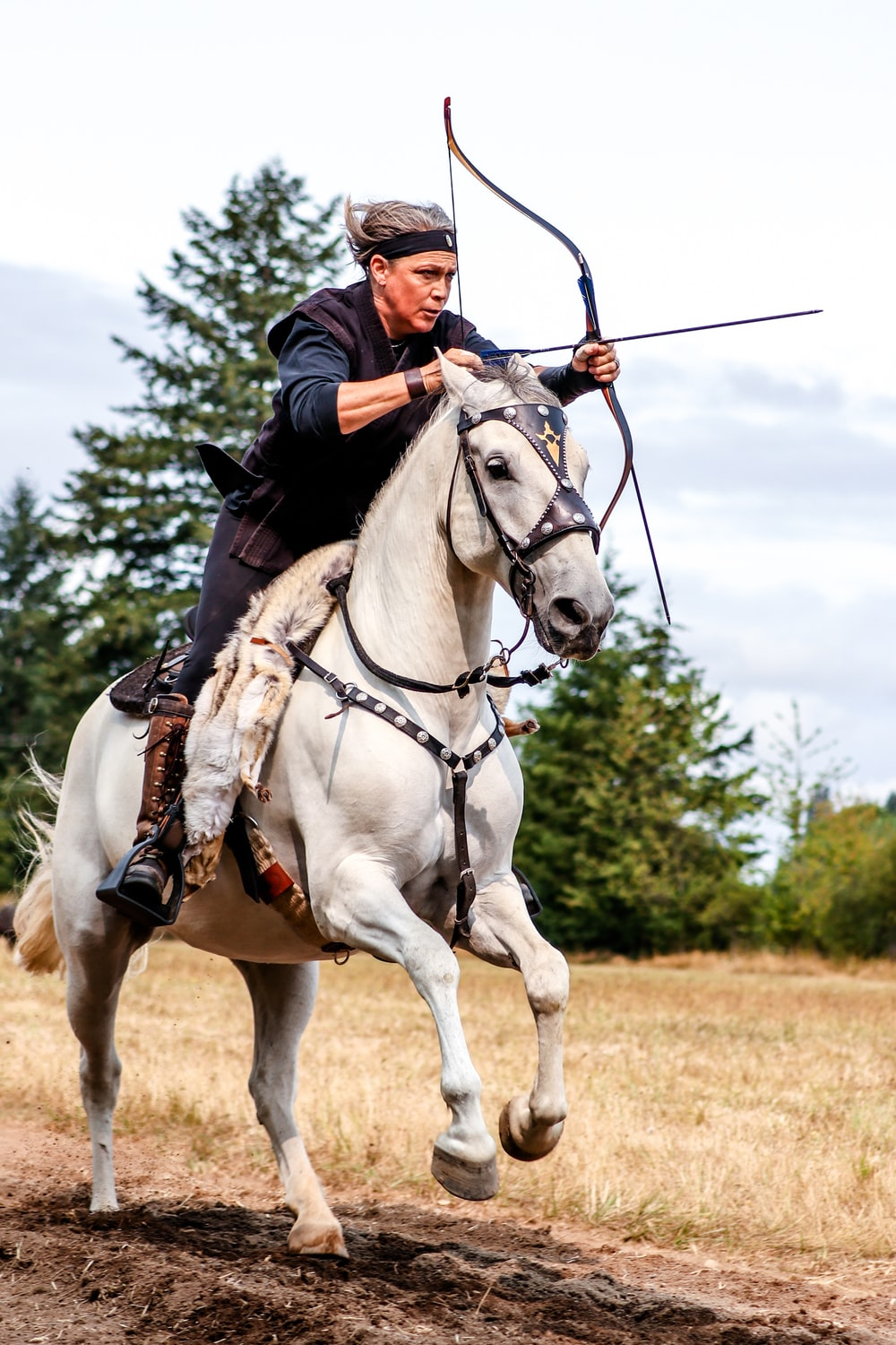 man riding white horse using composite bow
