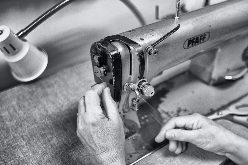 grayscale photo of person using sewing machine
