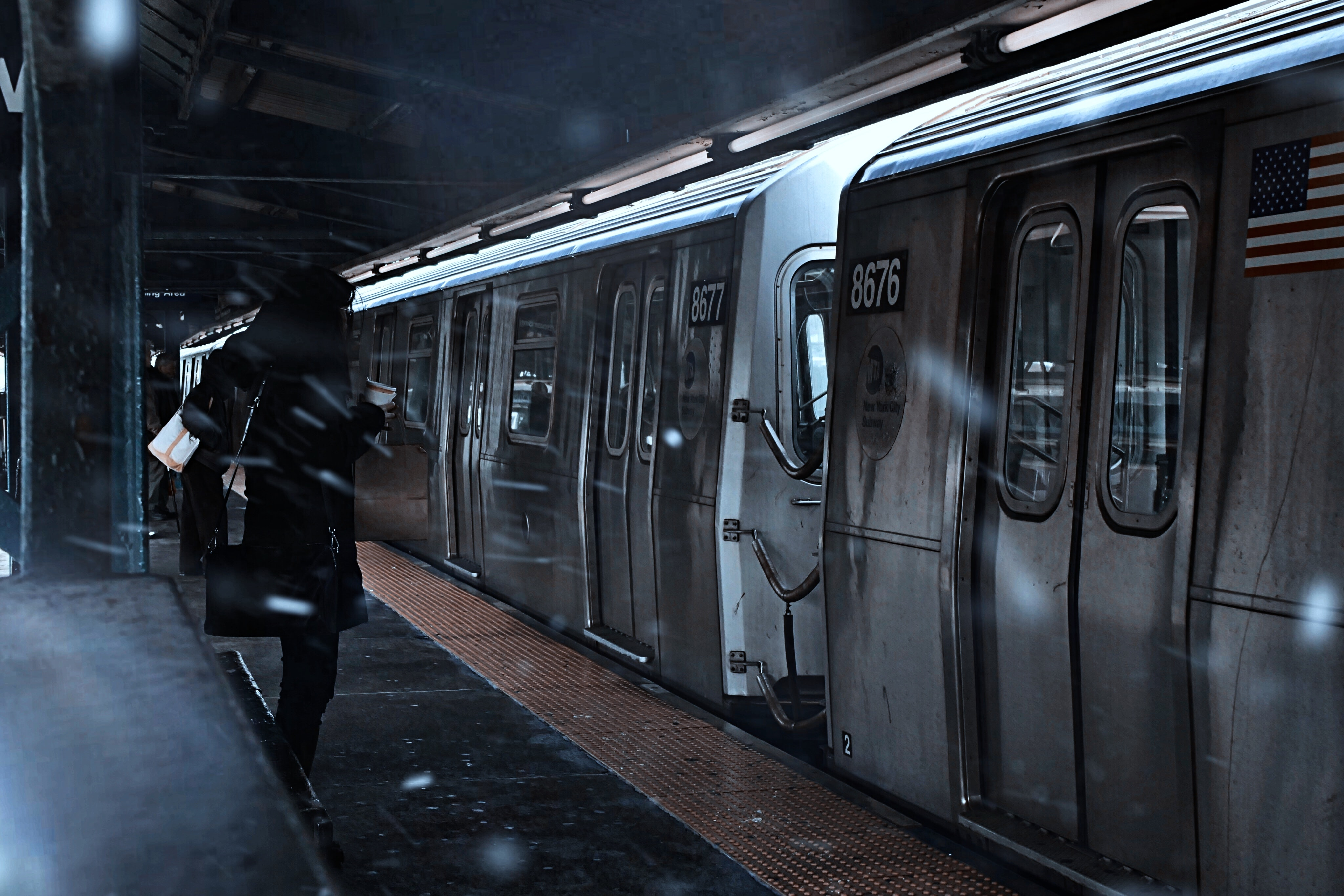 person in black jacket standing in the subway near train