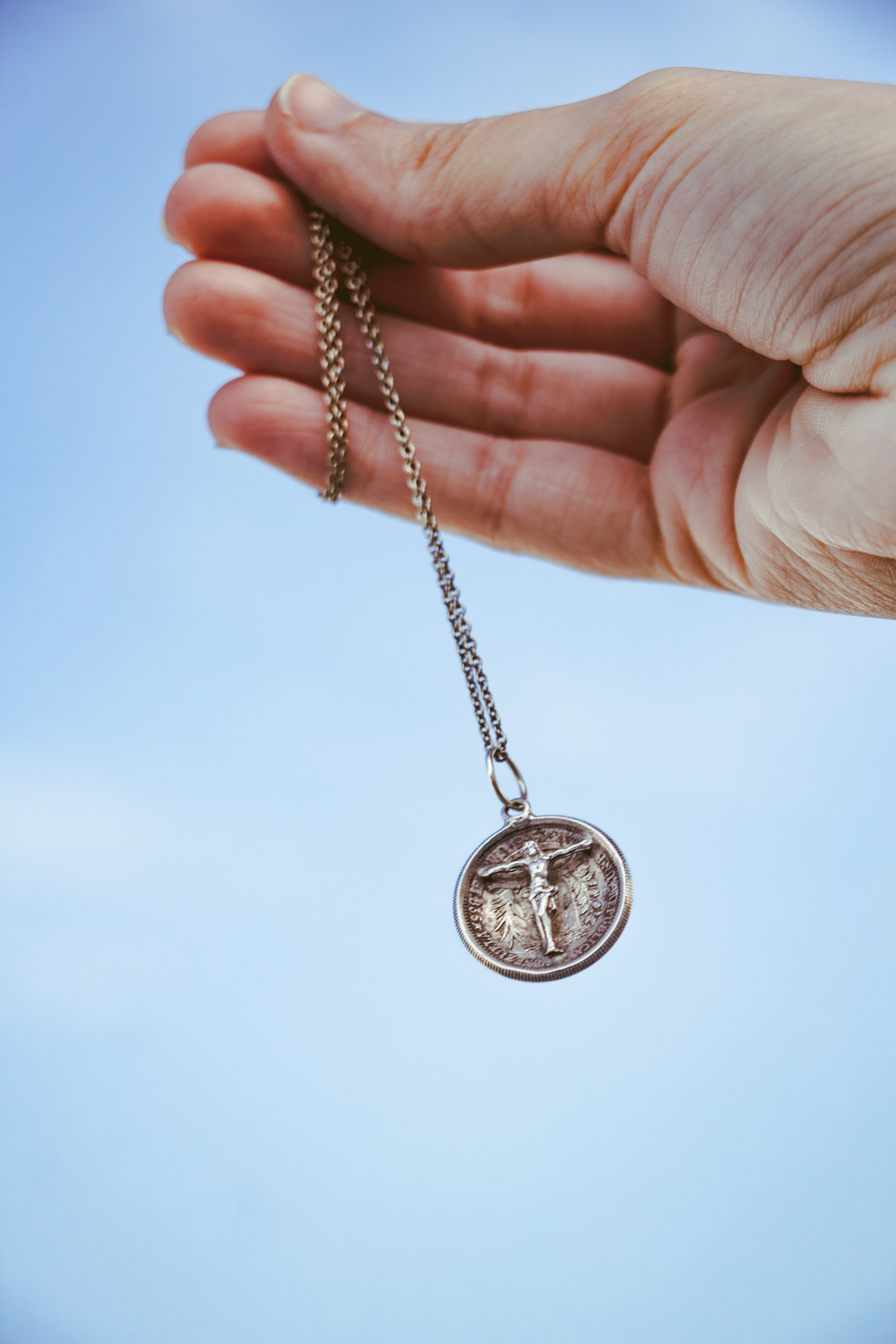 person holding pendant necklacec
