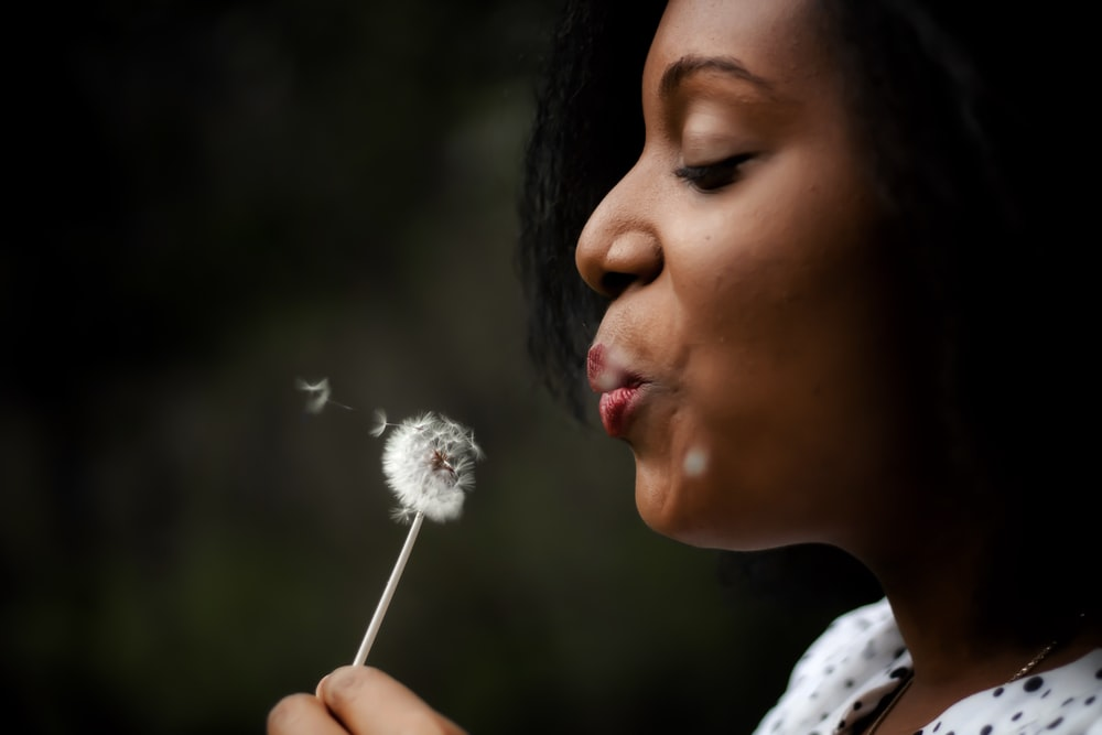 woman in white top blowing dandelion