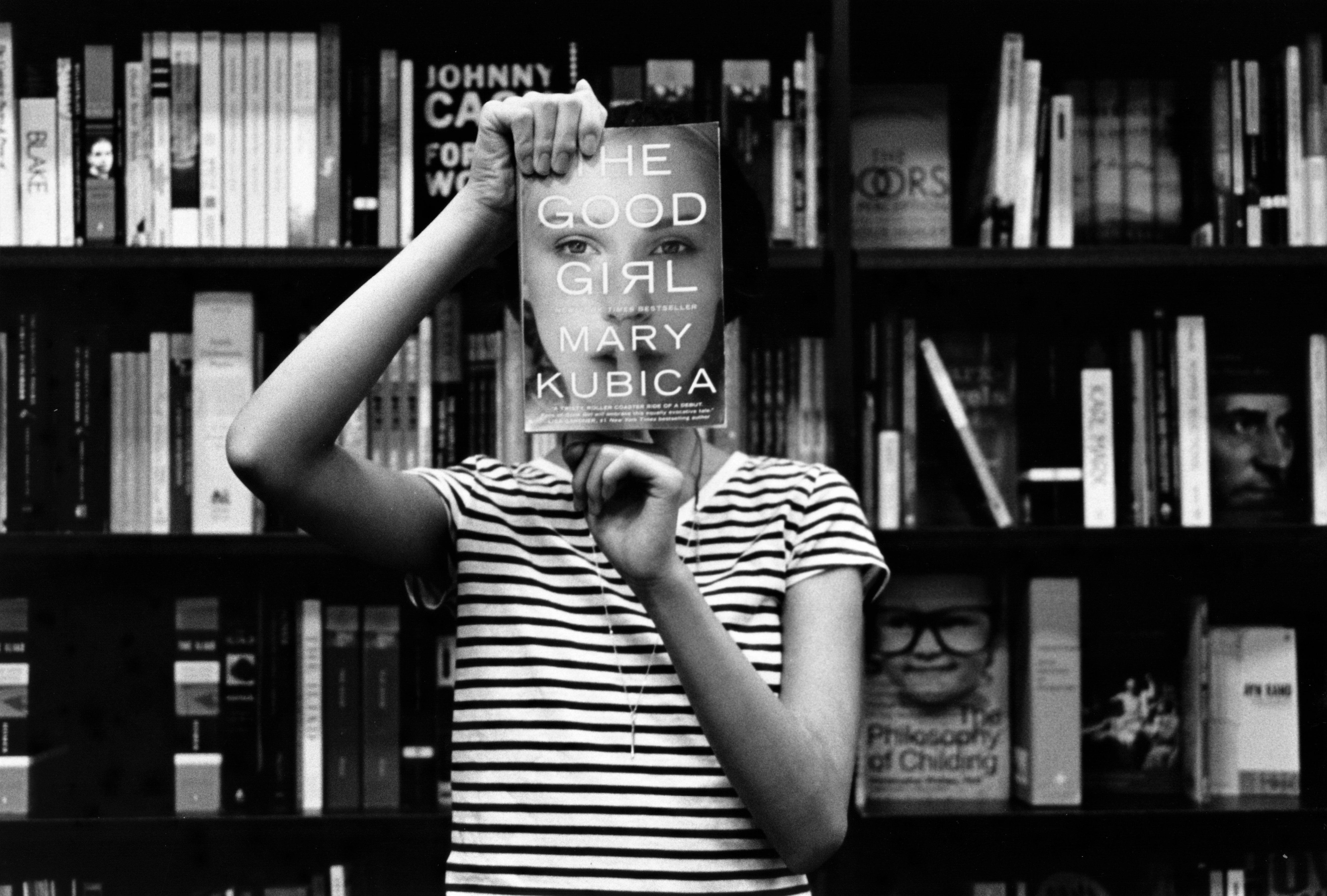 woman in striped shirt holds book in library