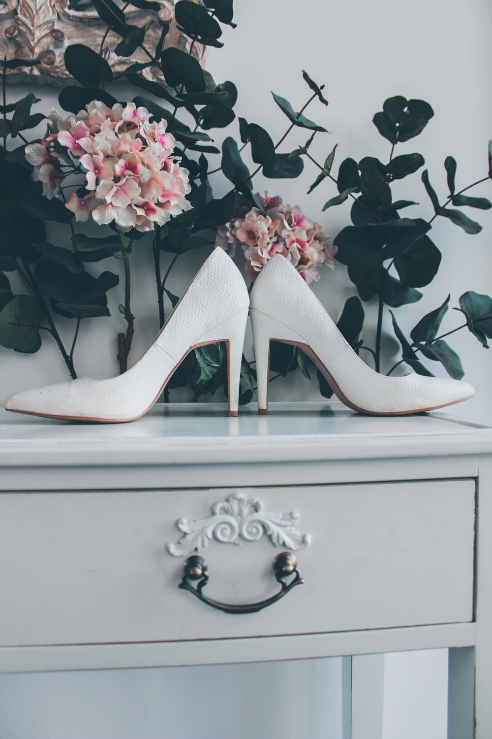white leather sandals on cabinet