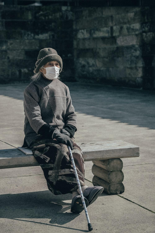 woman wearing face mask holding walking stick sitting on concrete bench