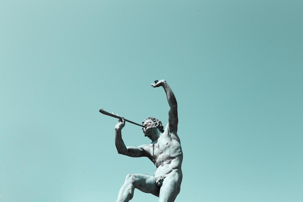 man using musical instrument statue
