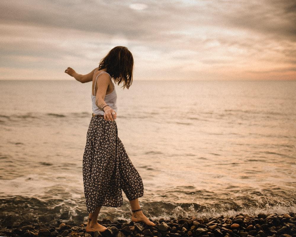 woman walking on rocks in beach