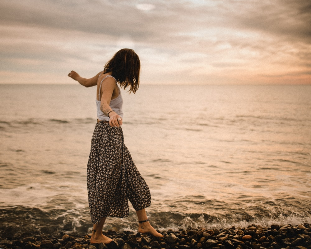 woman walking on rocks in beach