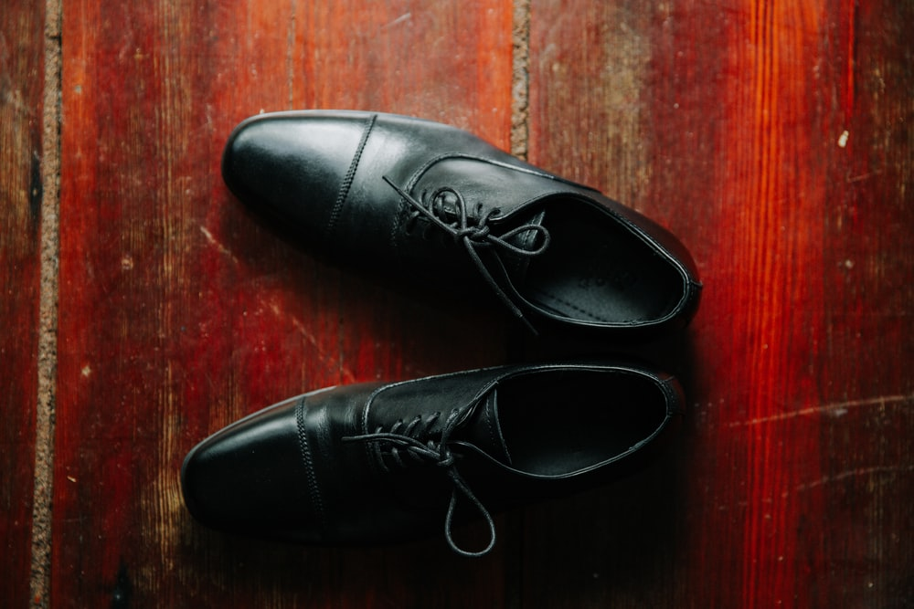 pair of black leather lace-up dress shoes on brown wooden surface