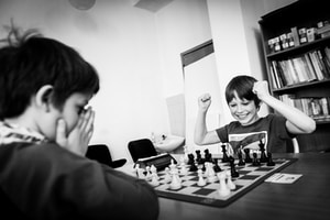 two boy playing chess grayscale photo
