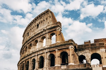 Colosseum under white clouds during daytime