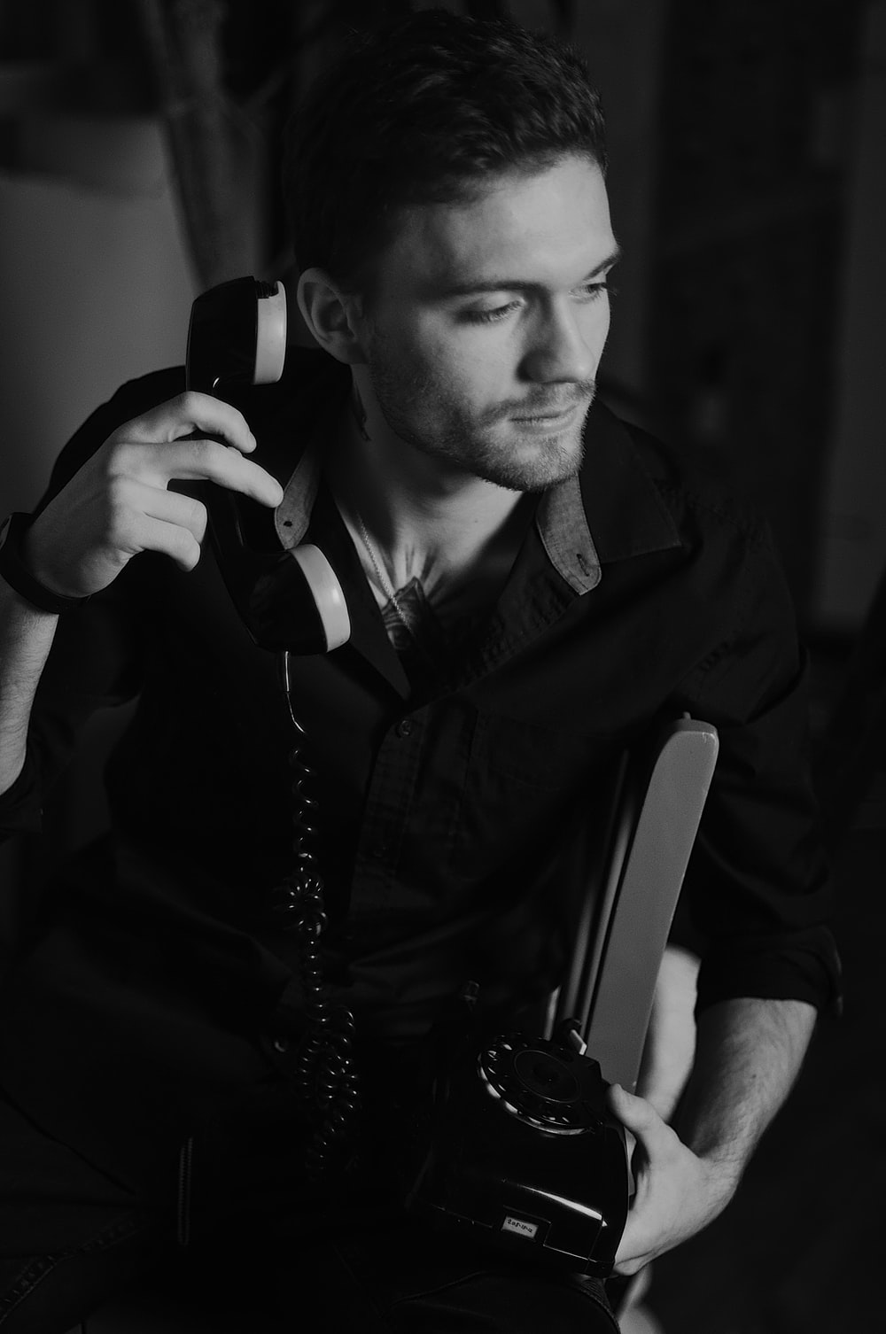 grayscale photo of man holding telephone