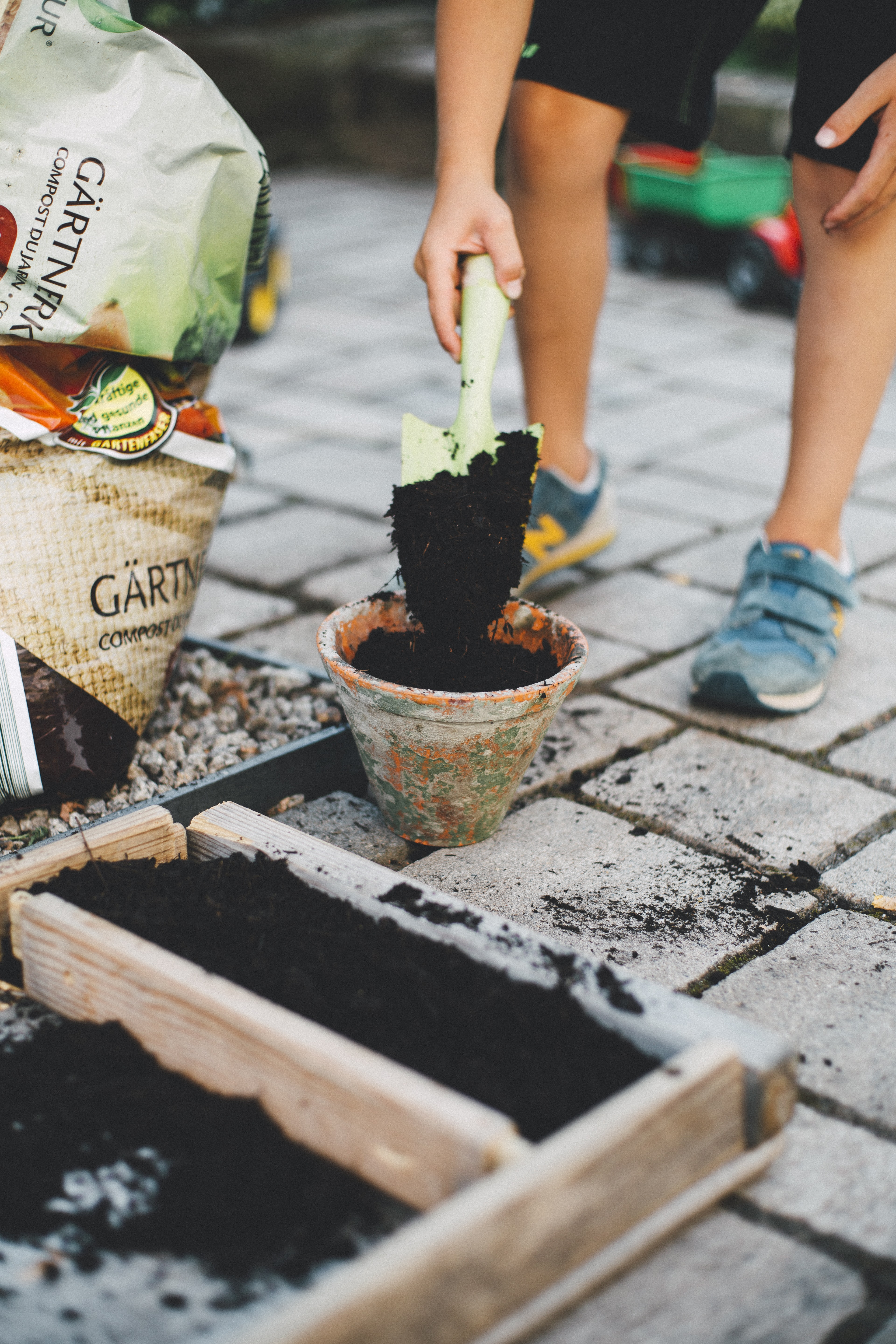 person putting soil inside brown planter