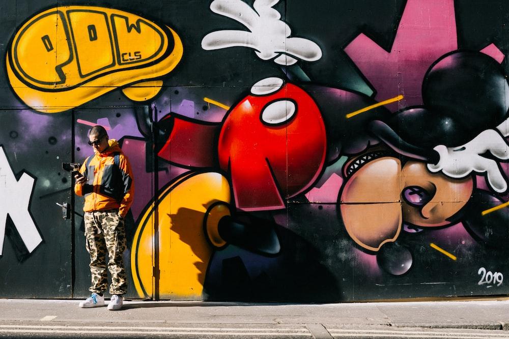 man standing beside Mickey Mouse graffiti painted wall