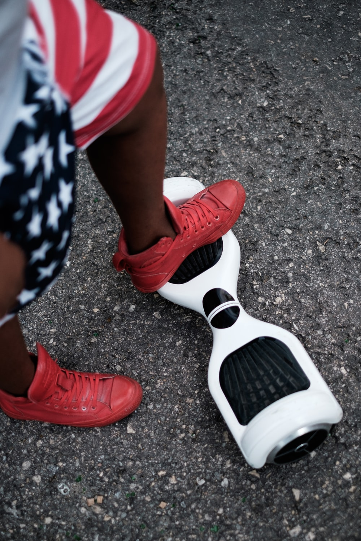 person riding self balancing board on concrete pavement