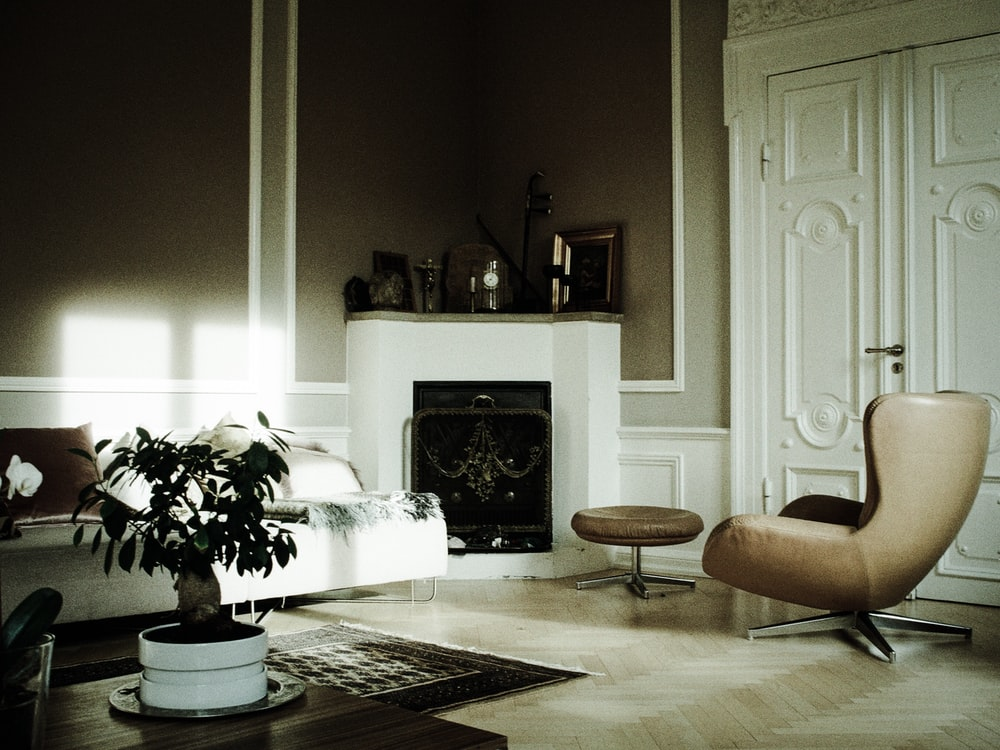 brown rolling chair in front of fireplace