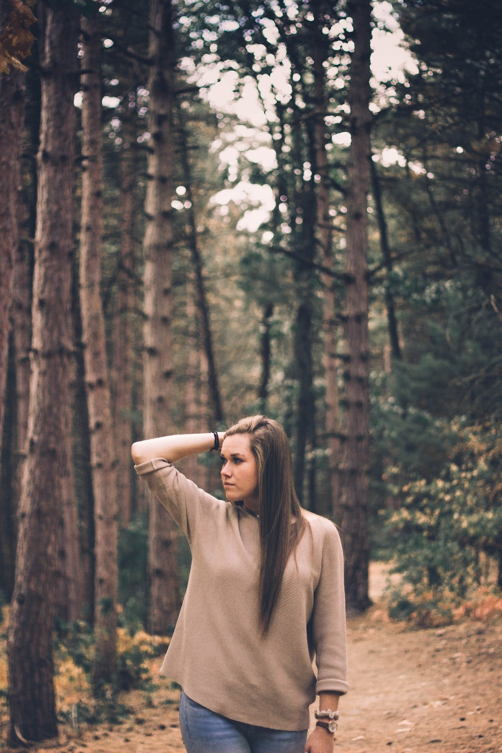 woman standing under green trees