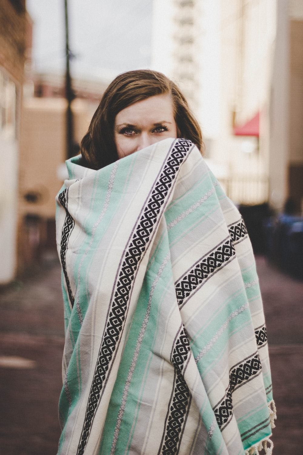 woman covering her body of teal blanket