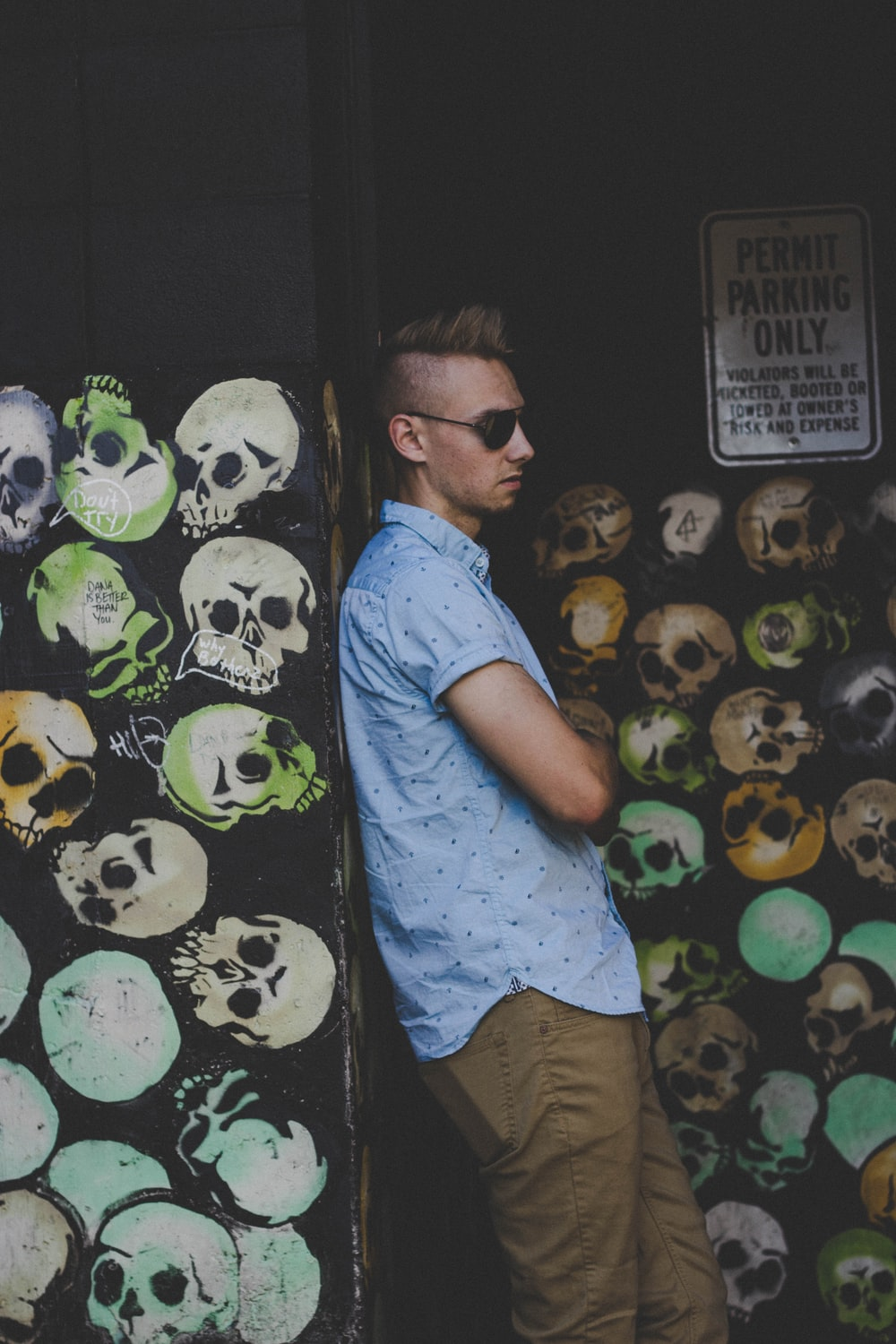 man leaning on skull painted wall wearing black sunglasses