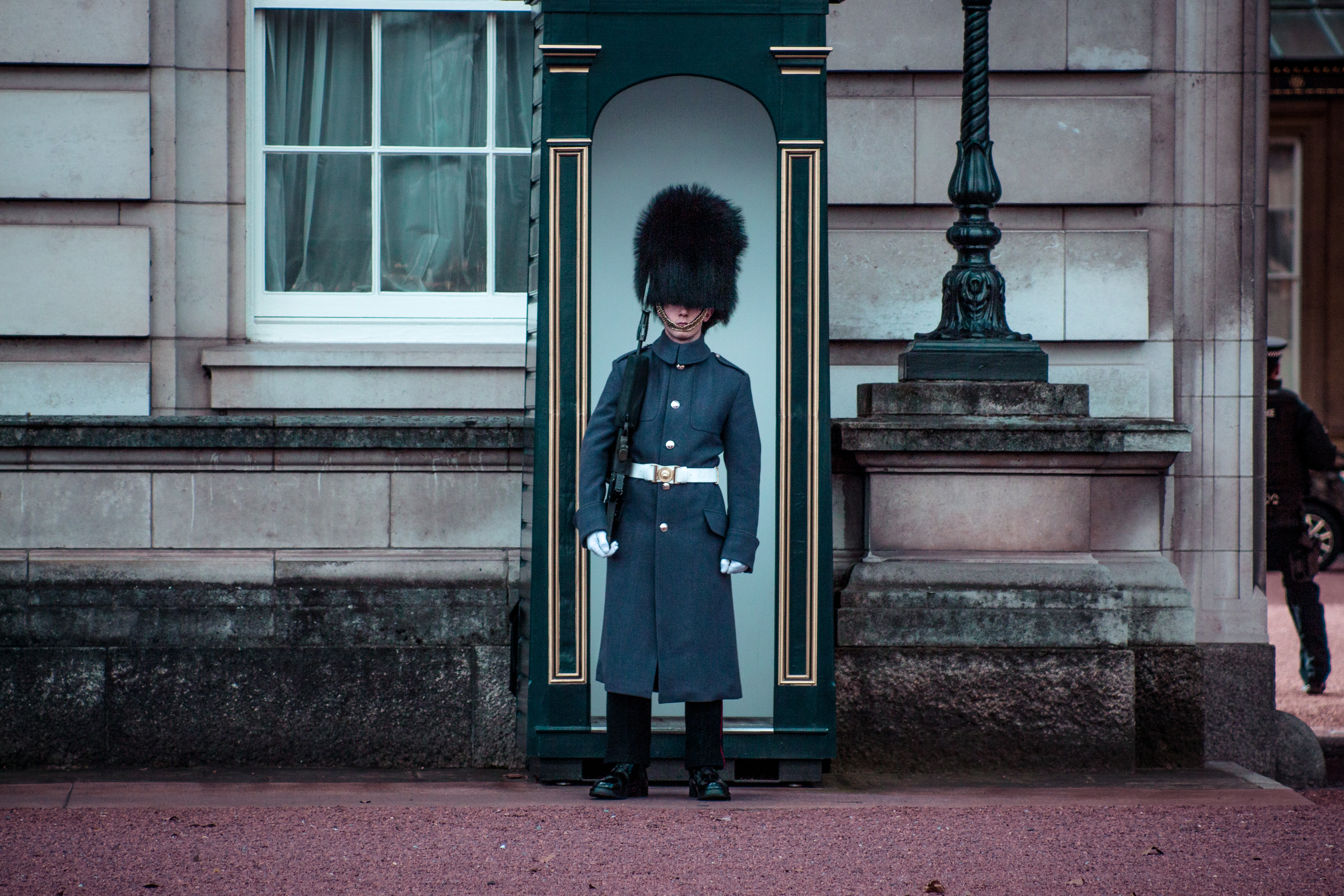man standing beside gray house