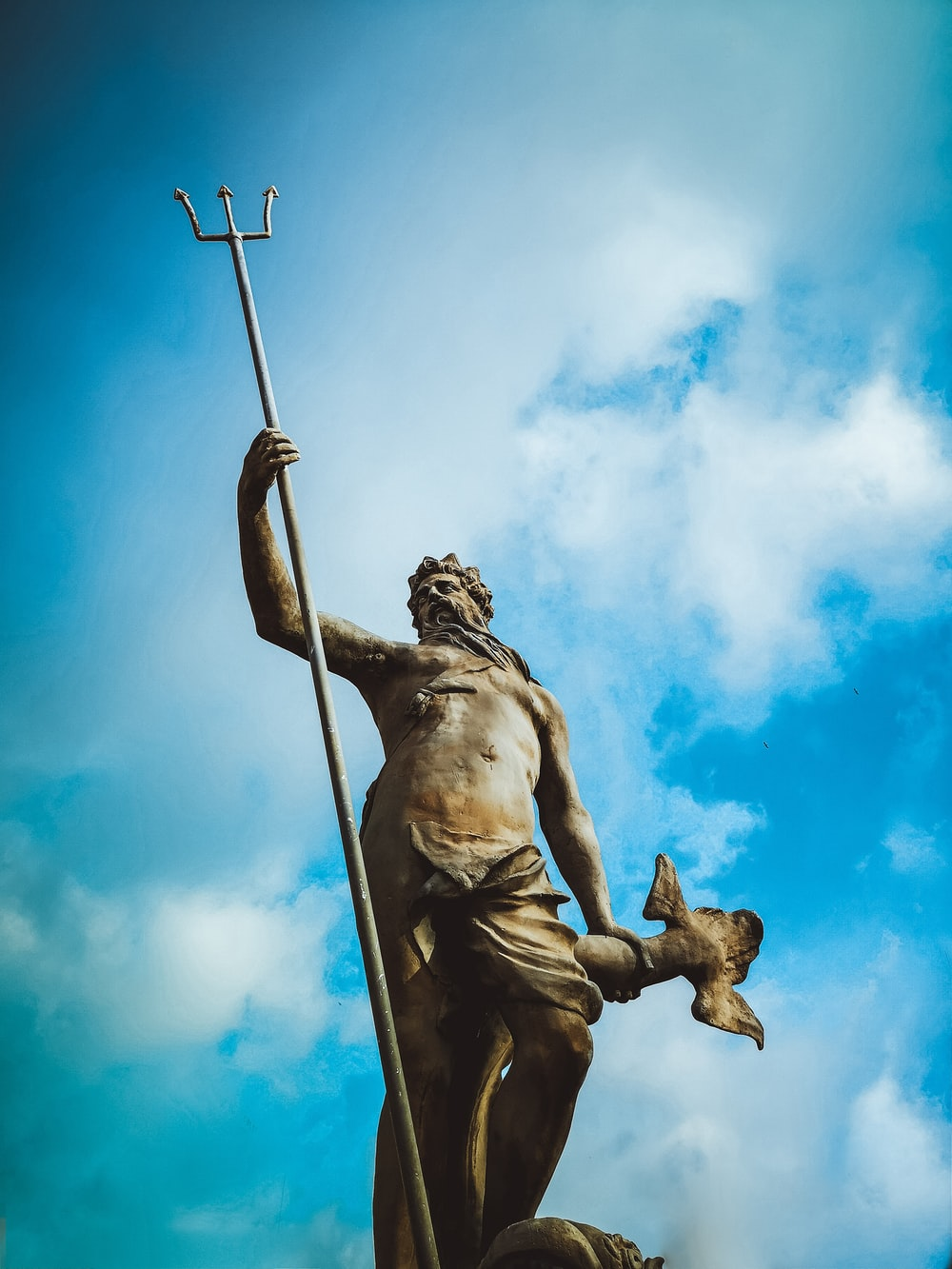 man holding trident statue under white clouds at daytime