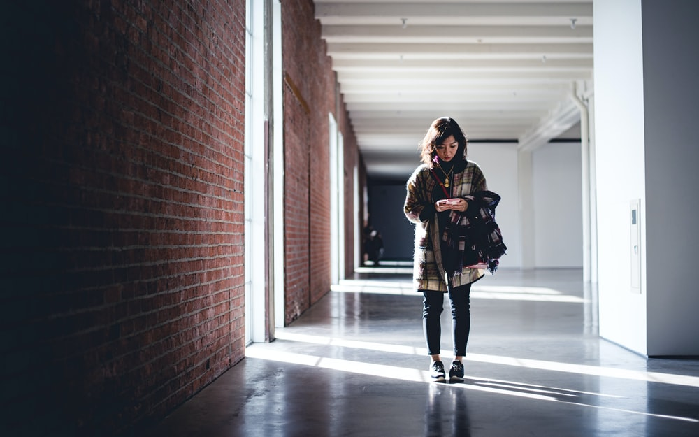 woman wearing black and brown jacket standing in building