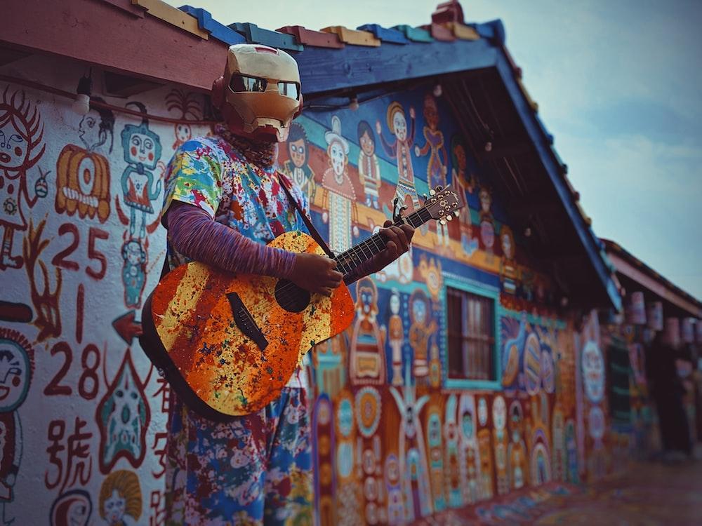 man wearing brown face mask holding guitar