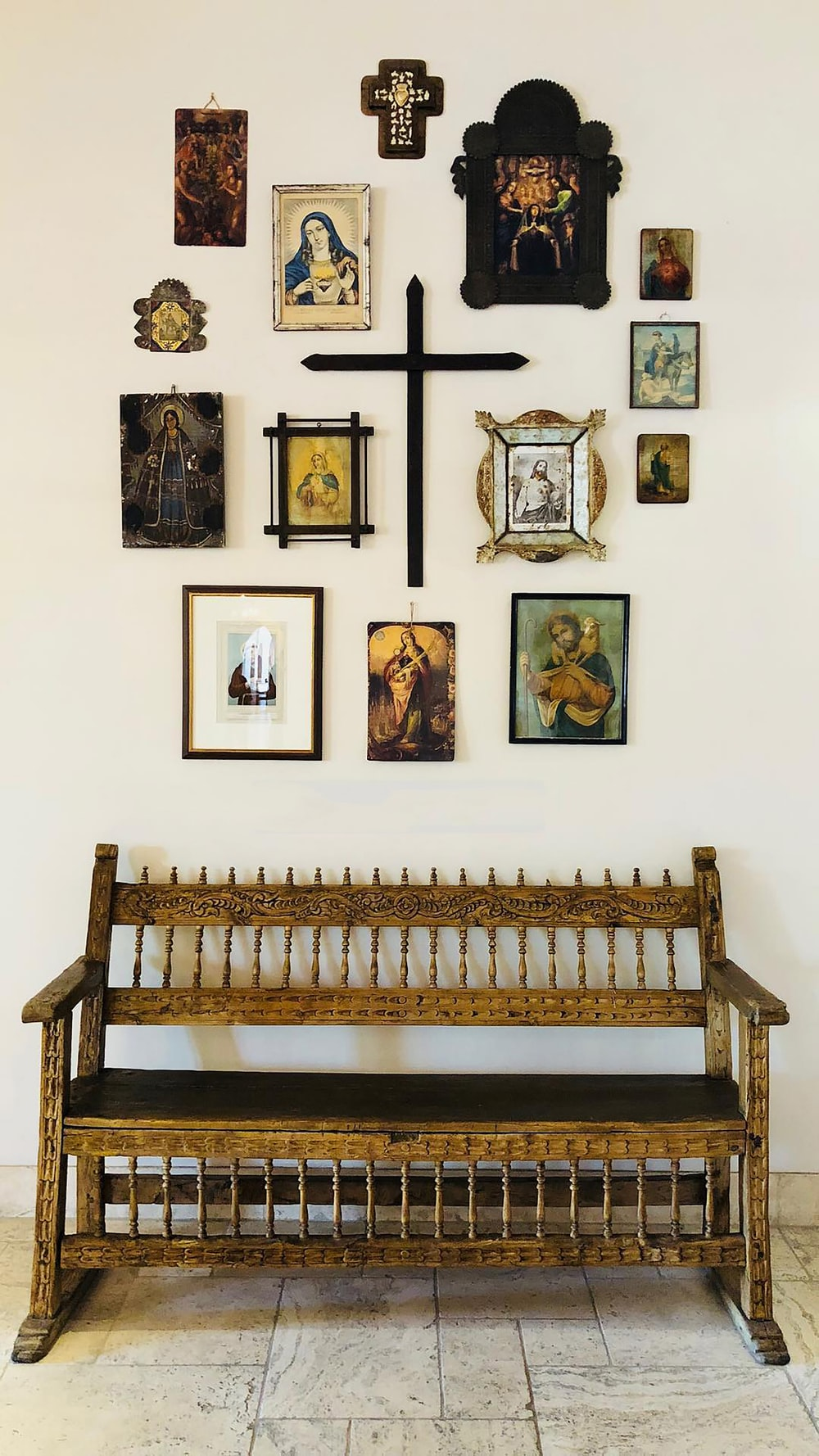 brown wooden bench with religious wall decors