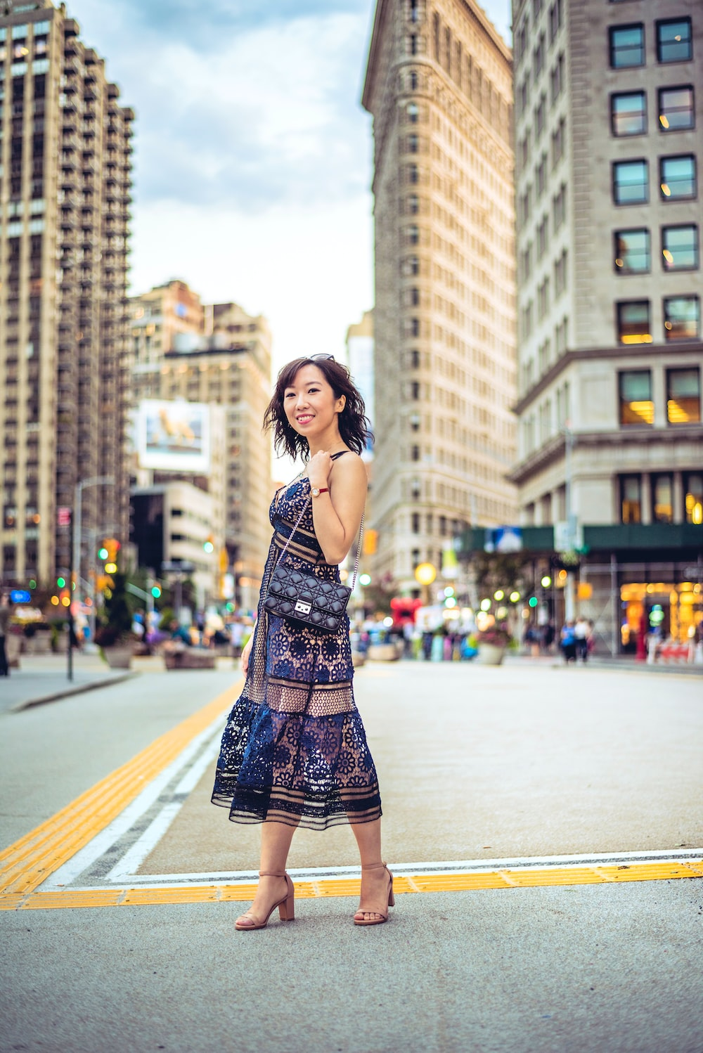 woman standing in center of street near buildings
