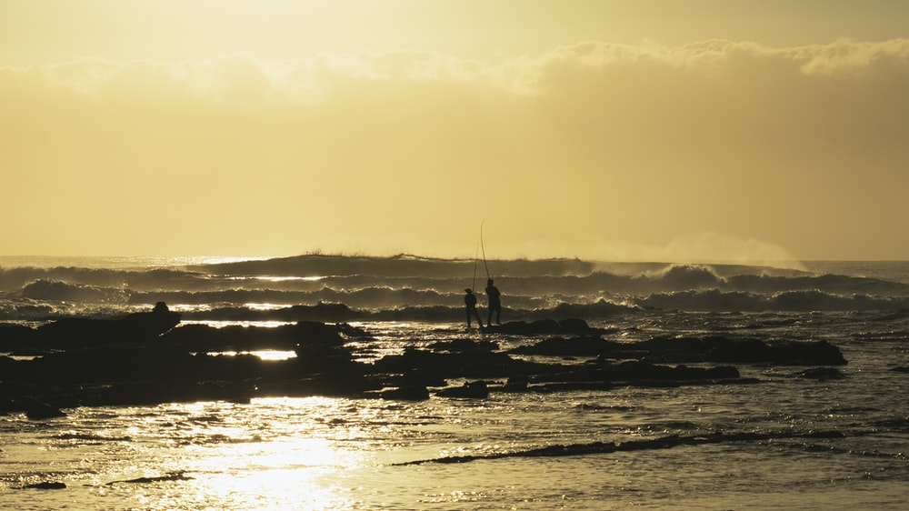 two people fishing at sea during sunset
