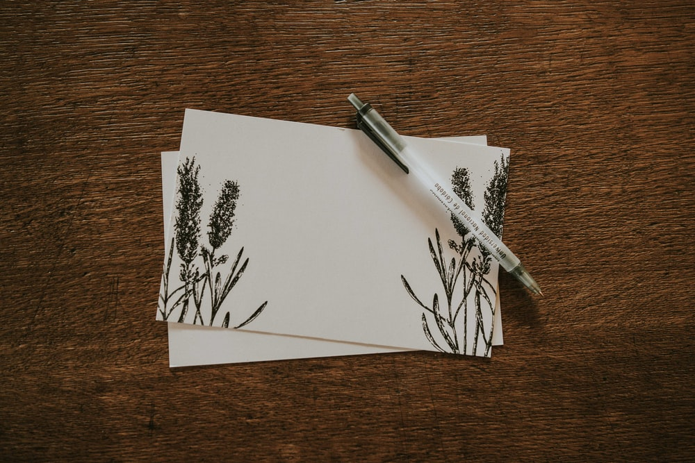 white pen on top of two white and black floral stationeries