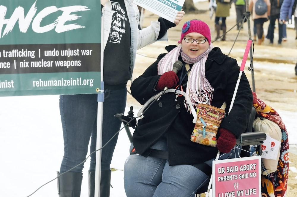 woman sitting next to signage