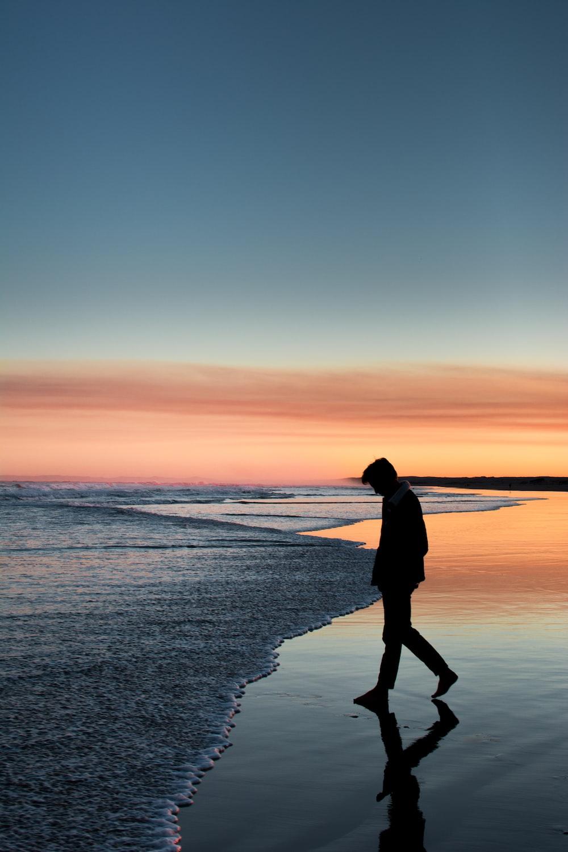 silhouette of man walking on seashore under orange sky