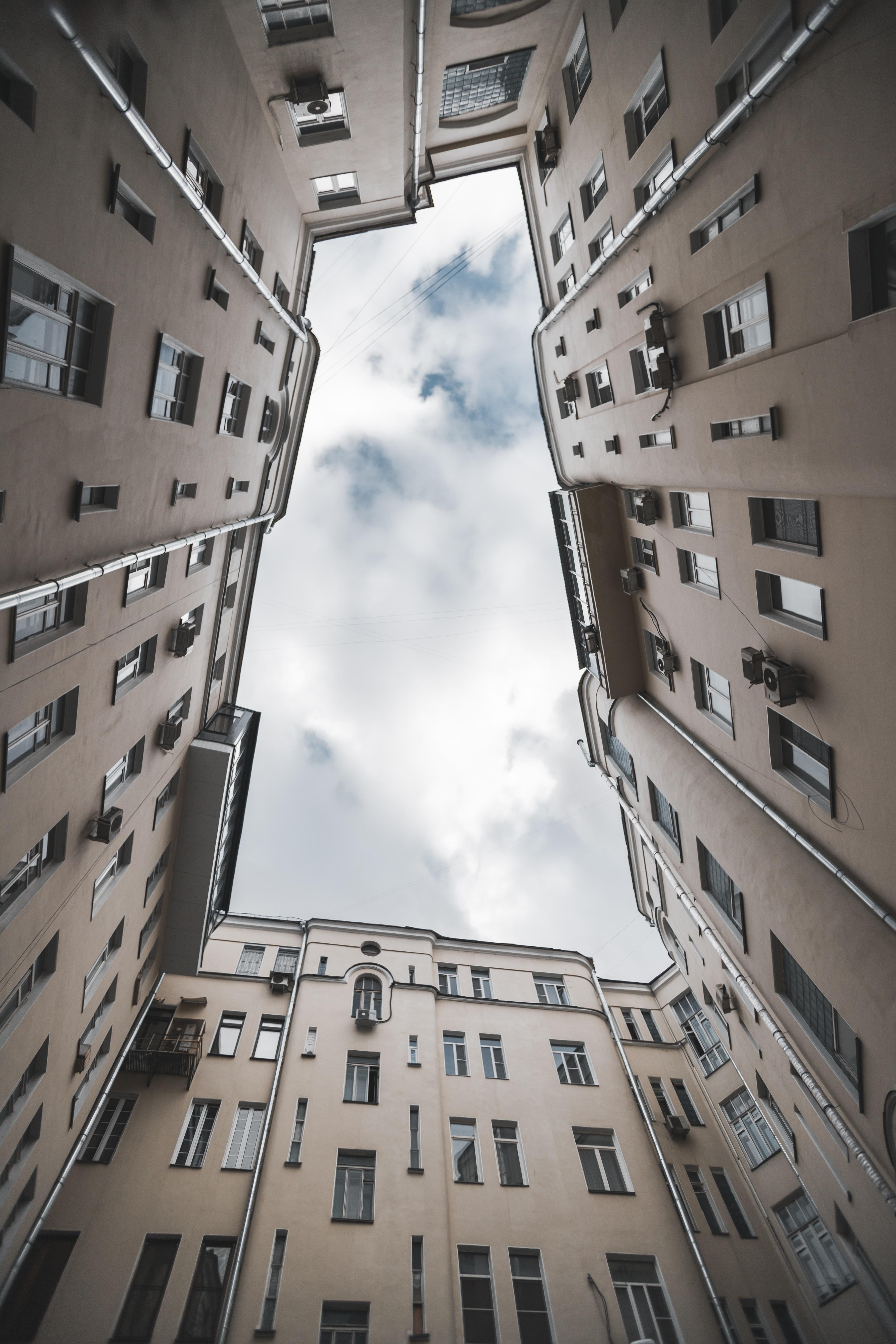 brown concrete building under white clouds