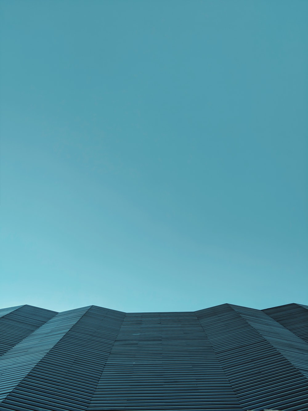 low-angle photography of gray structure under calm blue sky