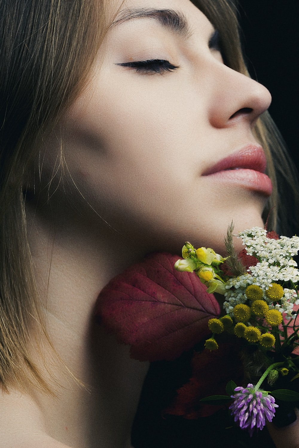 woman closing her eyes next to flowers