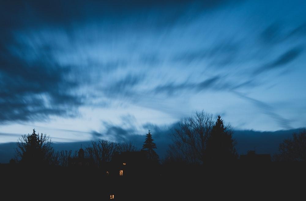 grey cloudy sky over lighted house