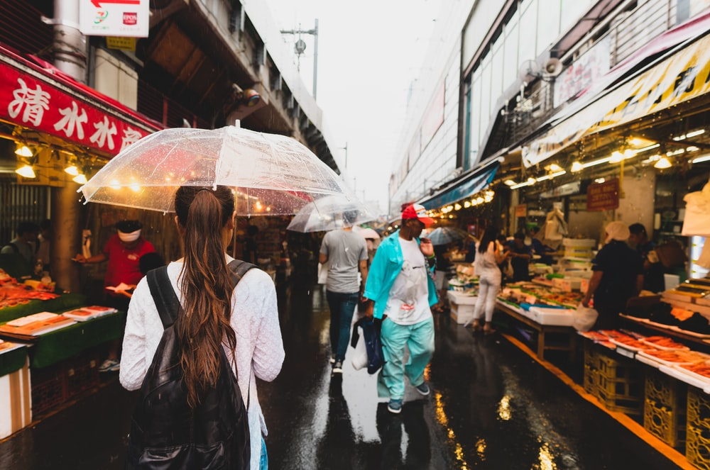 people walking with umbrella on alley between store stalls