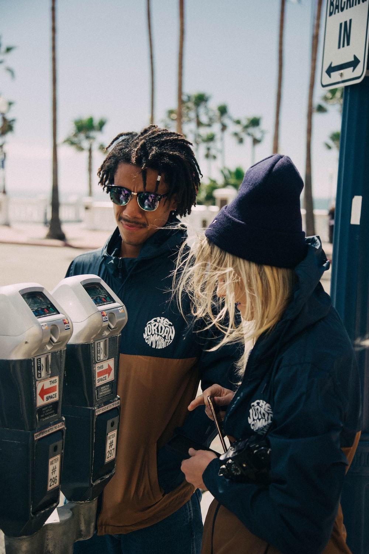 man and woman standing beside parking meters