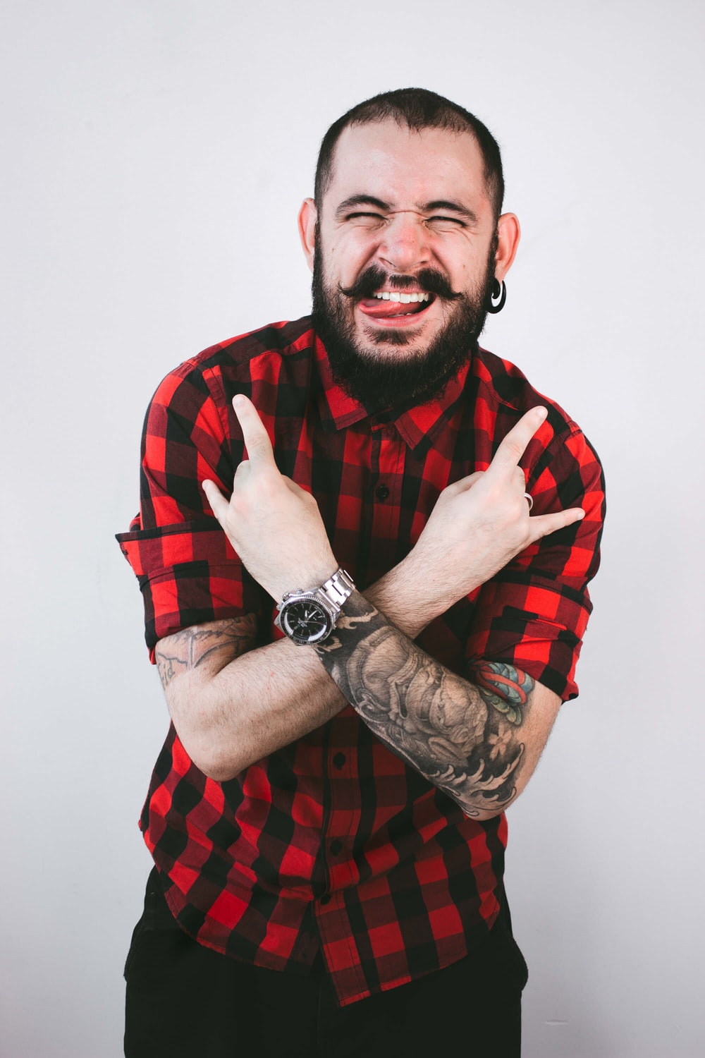 man wearing red and black checked button-up shirt doing rock hand sign