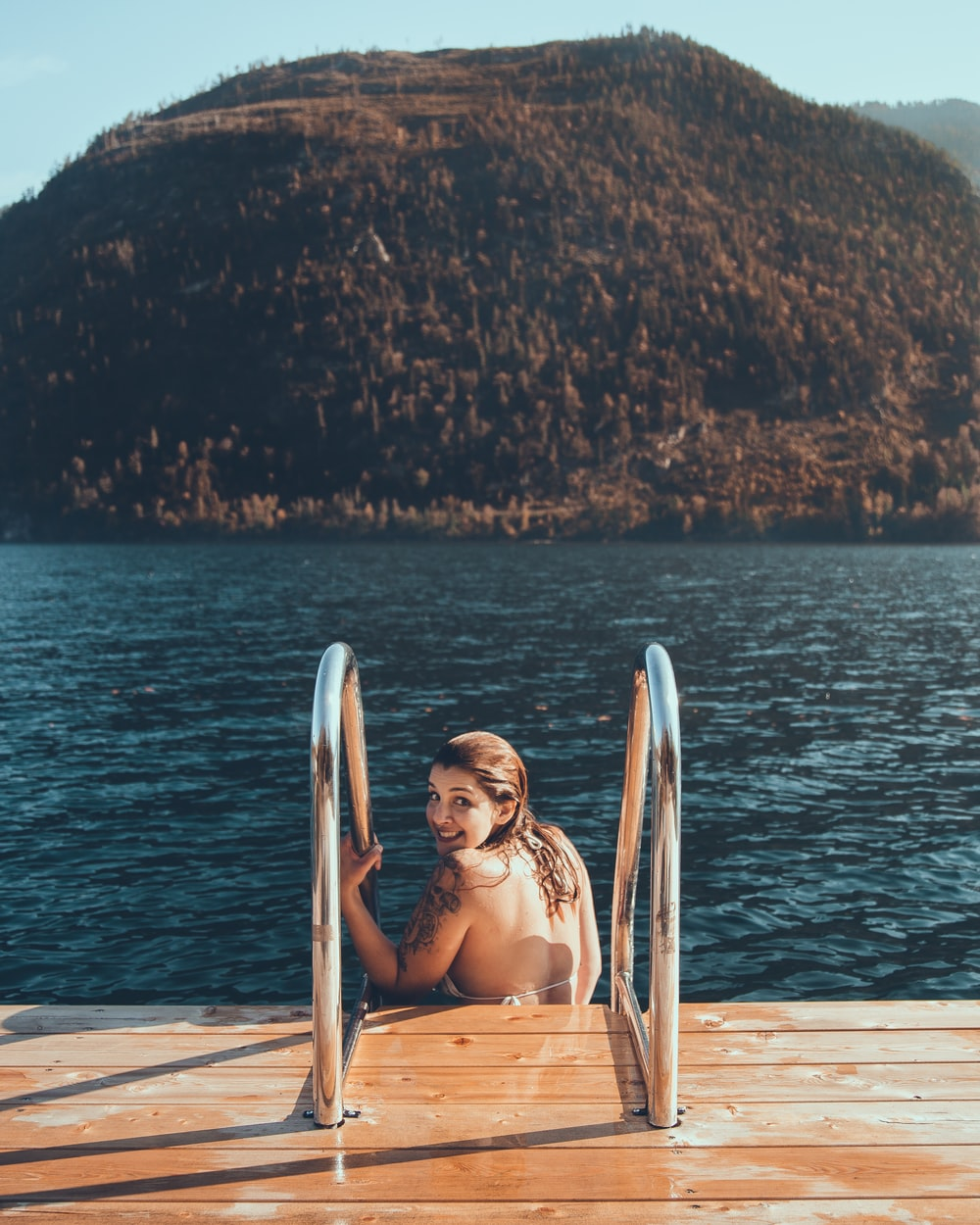 woman wearing white bra sitting on stairs near body of water