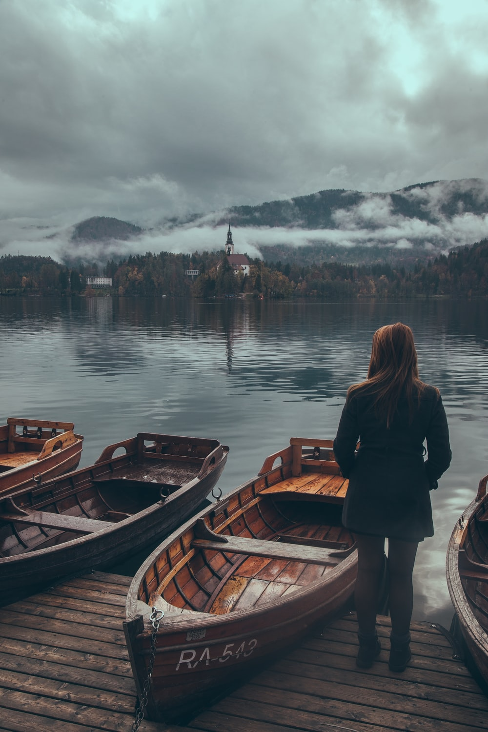woman standing by the wooden boats at the lake under grey cloudy sky
