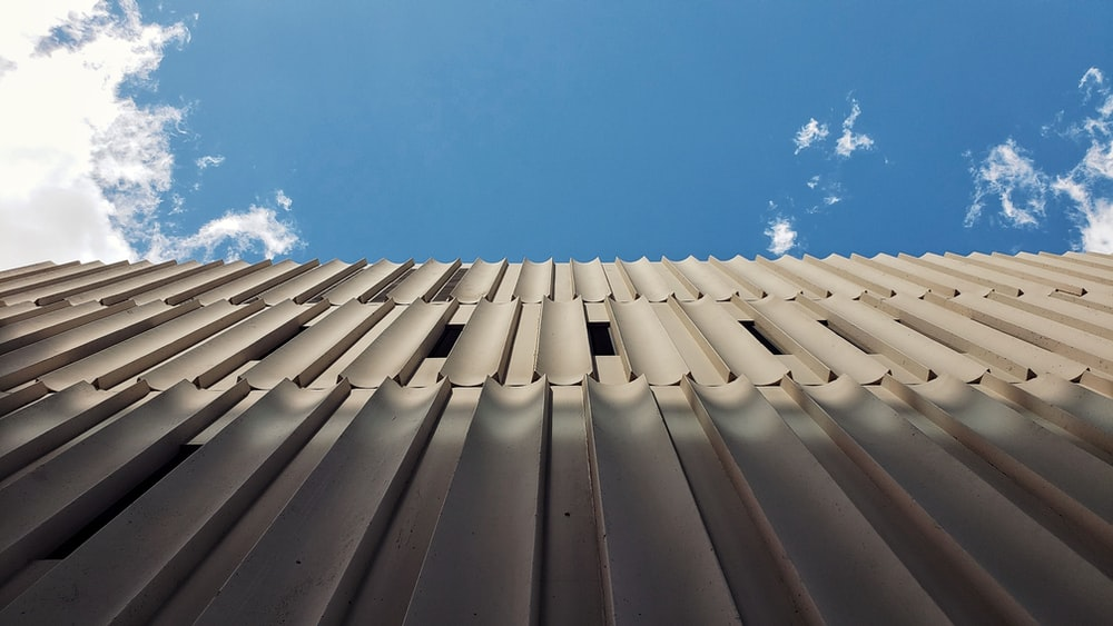 low angle photography of beige concrete building during daytime