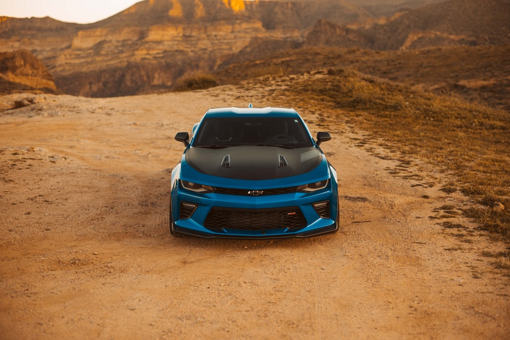 blue car parked beside rock formation