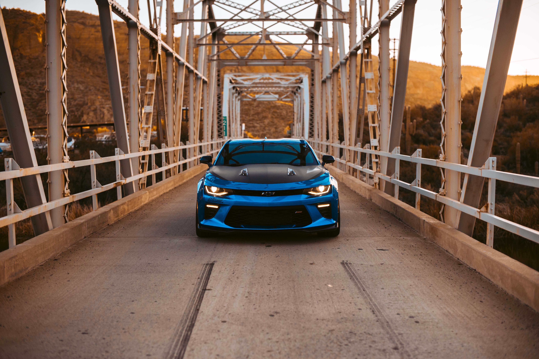 blue vehicle on bridge