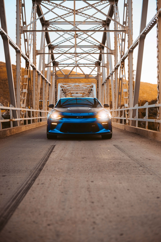 blue Chevrolet Camaro running on bridge during daytime