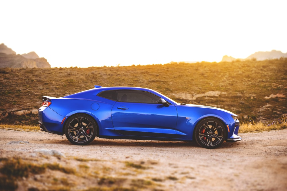 blue coupe on road during daytime