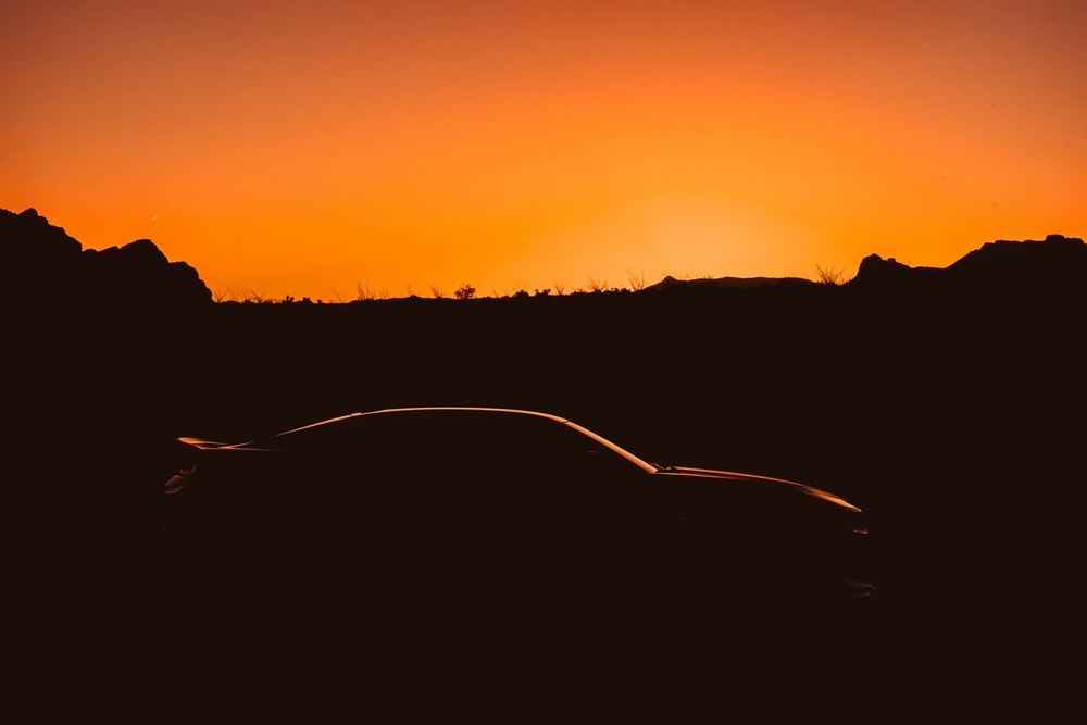 silhouette of sports car on park during sunset